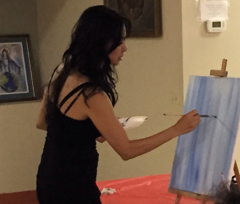 Art instructor Vangie Rodriguez works on the art for the evening's class.